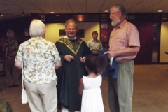 Fr. Gerry greets parishioners in lobby of OMI